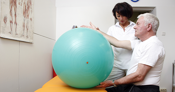 Foto: Physiotherapie mit Gymnastikball und Senior